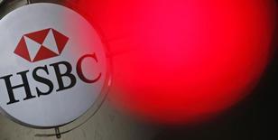 Una luz roja de un semaforo brilla cerca del logo del banco HSBC, en Paríss, 15 de junio de 2015. HSBC, el mayor banco europeo, canceló sus planes para congelar salarios este año aunque sigue cauteloso sobre las perspectivas de sus ingresos, según un memorando del presidente ejecutivo Stuart Gulliver visto por Reuters el jueves. REUTERS/Christian Hartmann