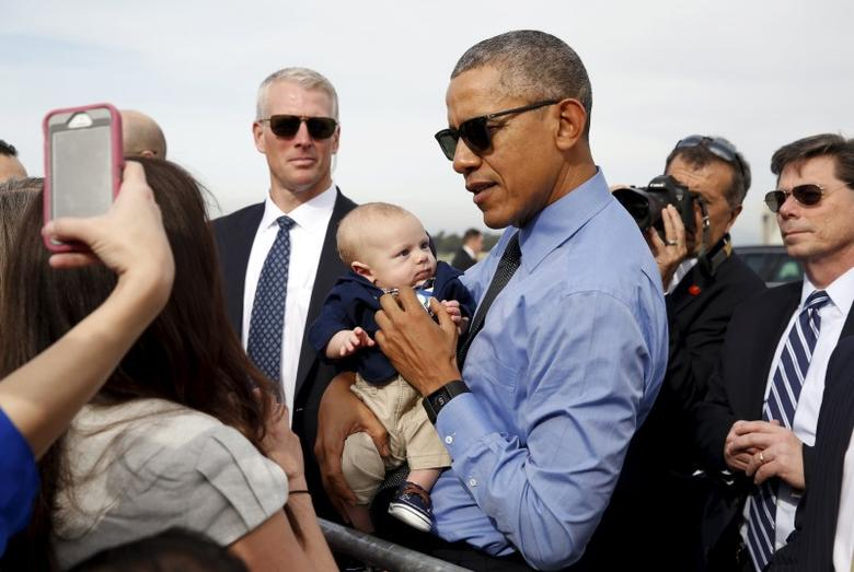 U.S. President Barack Obama poses with a baby before boarding Air Force One as he departs from Moffett Field in Mountain View, California February 11, 2016.  Obama is traveling to Los Angeles.  REUTERS/Kevin Lamarque