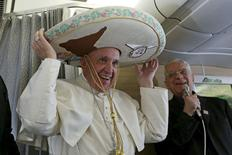 Папа римский примеряет сомбреро, подаренное мексиканским журналистом, на борту самолета перед вылетов в Гавану. 12 февраля 2016 года. Богатый владелец вещательной компании, который в детстве подрабатывал полировщиком обуви, чтобы помогать в одиночку растившей его матери, отполировал туфли папы римского Франциска на борту папского самолета в пятницу, отдав должное людям, борющимся с трудностями, чтобы прокормить свои семьи. REUTERS/Alessandro Di Meo/Pool