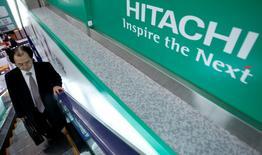 A shopper rides an escalator past a logo of Hitachi Corp at an electronics retail store in Tokyo February 3, 2014. REUTERS/Yuya Shino