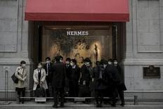 La economía japonesa se contrajo a una tasa anualizada del 1,4 por ciento en el cuarto trimestre del 2015, mostraron el lunes datos del gobierno. En la foto, un grupo de empleados busca refugio ante la lluvia delante de una tienda de lujo en Tokio el 15 de febrero de 2016. REUTERS/Thomas Peter