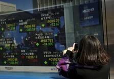 El Ibex-35 continuaba su rebote por segundo día, en línea con las demás plazas europeas, tras la fuerte subida registrada esta madrugada por las bolsas asiáticas. En la imagen, una mujera toma fotos de una pantalla con los niveles de los índices bursátiles en el exterior de una casa de valores en Tokio, 10 de febrero de 2016. REUTERS/Thomas Peter