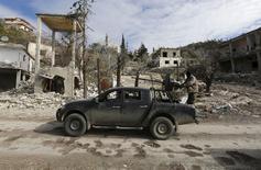 Бойцы сирийских правительственных сил в городе Рабия в провинции Латакия. 27 января 2016 года. В то время как российские самолеты бомбят позиции повстанцев на поле боя в Сирии, российские военные советники играют гораздо более тонкую роль в поддержке президента Башара Асада. REUTERS/Omar Sanadiki