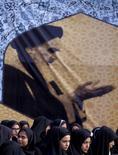 Иранские учащиеся собираются под портретом иранского духовного лидера аятоллы Хомейни в Тегеране 1 февраля 2016 года. Иран не спешит подтверждать делом заявление своего министра о солидарности с решением крупнейших нефтепроизводителей остановить добычу на текущих уровнях - решение, подтолкнувшее вверх цены на черное золото и укрепившее валюты ряда сырьевых экономик. REUTERS/Raheb Homavandi