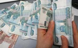 Работник небольшого красноярского магазина считает деньги. 26 декабря 2014 года. Рубль показывает в основном отрицательную динамику на торгах четверга, невзирая на рост нефти, что участники рынка увязывают с фиксацией прибыли в спекулятивных позициях после сильного укрепления рубля накануне до февральских максимумов, а также из-за опасений хрупкости текущего нефтяного ралли. REUTERS/Ilya Naymushin