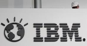 Un trabajador fotografiado detrás del logo de IBM en la feria de computación CeBIT, en Hanover, Alemania. 26 de febrero de 2011. International Business Machines Corp dijo que comprará a la firma Truven Health Analytics, proveedor de datos de cuidados de la salud en Internet, por 2.600 millones de dólares, la cuarta adquisición de IBM relacionada a la salud desde que lanzó la unidad Watson Health en abril del año pasado. REUTERS/Tobias Schwarz