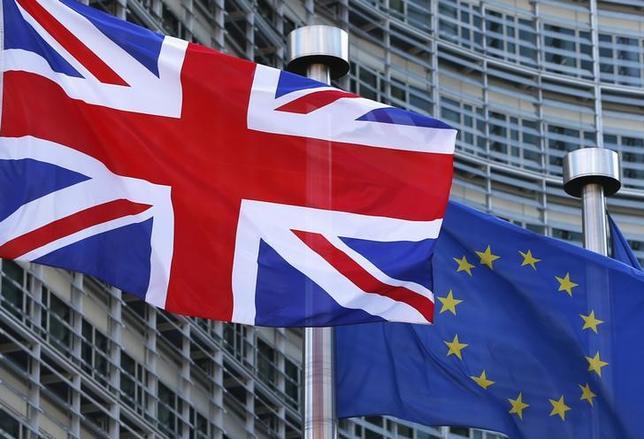 2月22日、イタリアのレンツィ首相は、英国が今年の国民投票でEU離脱を決めれば、EUの市民よりも英国の市民に大きな悪影響が及ぶとの見方を示した。写真は英国国旗(右)とEUの旗、ブリュッセルで16日撮影(2016年 ロイター/Yves Herman)