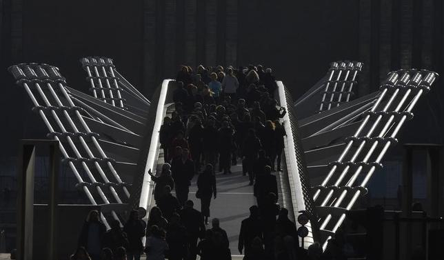 Workers are seen walking over the Millennium footbridge during the lunch hour in the City of London, in Britain, January 21, 2016. REUTERS/Toby Melville
