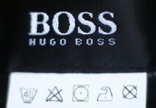 The logo of German fashion house Hugo Boss is seen on a clothing label at their outlet store in Mezingen near Stuttgart October 29, 2013. German fashion house Hugo Boss said it was expecting a strong final quarter as it reported on Thursday third-quarter sales that fell short of expectations due to currency effects. Picture taken October 29, 2013. REUTERS/Michael Dalder (GERMANY  - Tags: FASHION BUSINESS LOGO) - RTX14UV5
