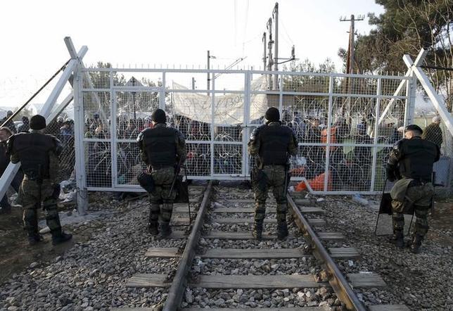 2月23日、ギリシャは、西欧への主要な陸路を閉ざそうとするバルカン諸国によって足止めを食らう難民が、自国に大挙して戻ってくることを恐れて、マケドニアと接する北部の国境地帯から難民たちをバスに乗せ、移動させ始めた。写真は難民と対峙するマケドニアの警官。ギリシャとマケドニアの国境で撮影(2015年 ロイター/Marko Djurica)