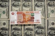 Рублевые и долларовые купюры в Сараево 9 марта 2015 года. Рубль на послепраздничной биржевой сессии среды показывает отрицательную динамику на фоне нефти, значительно подешевевшей накануне и снижающейся сейчас из-за опасений сохранения её переизбытка на мировых рынках. REUTERS/Dado Ruvic