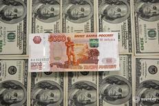 Рублевые и долларовые купюры в Сараево 9 марта 2015 года. Рубль на послепраздничной биржевой сессии среды показывает отрицательную динамику на фоне нефти, значительно подешевевшей накануне и падающей сейчас из-за опасений сохранения её переизбытка на мировых рынках. REUTERS/Dado Ruvic