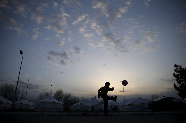 A migrant child plays with a ball near the town of Polikastro, Greece February 23, 2016. REUTERS/Marko Djurica