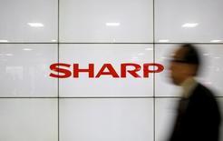 Un hombre pasa frente a un cartel con el logo de Sharp Corp en Tokio, Japón, el 25 de febrero de 2016. Sharp aceptó el jueves ser comprada por Foxconn, en la que sería la mayor adquisición de una empresa japonesa de tecnología por parte de una firma extranjera, aunque la compañía taiwanesa dijo que necesitaba aclarar algunos términos del acuerdo. REUTERS/Yuya Shino