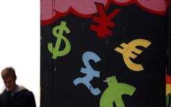 Символы различных валют на стене в Дублине 22 октября 2014 года. Доллар опустился в пятницу, и тем не менее взял курс на подъём за неделю к основным валютам, а внимание инвесторов было приковано к двухдневным переговорам стран G20, которые начались в Шанхае. REUTERS/Cathal McNaughton