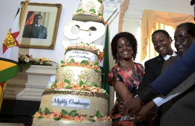 Zimbabwean President Robert Mugabe (R) is helped by his wife Grace (L) and son Chatunga (C) to cut a cake to celebrate his 92nd birthday at State House in Harare, February 22, 2016. Mugabe turned 92 on Sunday. REUTERS/Philimon Bulawayo