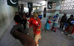 Anum, 17, punches padding with her coach Younus Qambrani while others observe during an exercise session at the first women's boxing coaching camp in Karachi, Pakistan February 20, 2016. REUTERS/Akhtar Soomro