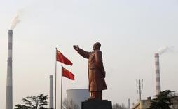"""Статуя Мао Цзэдунана фоне труб завода Wuhan Iron And Steel Corp в Ухане 6 марта 2013 года. Власти Китая планируют уволить порядка 5-6 миллионов государственных сотрудников """"предприятий-зомби"""" в ближайшие два-три года в рамках усилий, направленных на сокращение избыточных производственных мощностей, сказали два источника, близких к руководству страны. REUTERS/Stringer"""