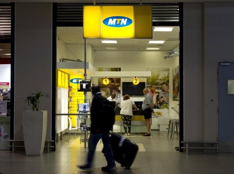Travellers walk past an MTN telecom shop at King Shaka International Airport in Durban, South Africa, November 16, 2015. REUTERS/Rogan Ward