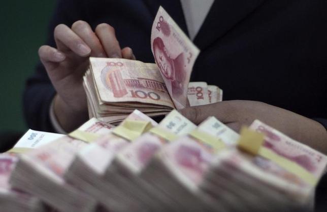 3月2日、中国が今年のマネーサプライM2伸び率の目標を13%程度に設定することが分かった。写真は湖北省保康県の銀行で人民元紙幣を数える行員。2007年11月撮影。(2016年 ロイター)