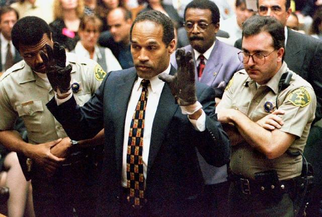 O.J. Simpson holds up his hands to the jury showing leather gloves that prosecutors say he wore the night of the murders of his ex-wife Nicole Brown Simpson and Ron Goldman during the Simpson double-murder trial in Los Angeles, California in this June 15, 1995 file photo. REUTERS/Sam Mircovich/Files