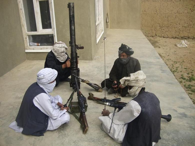 Taliban fighters pose with weapons as they sit in their compound at an undisclosed location in southern Afghanistan in this May 5, 2011 picture. REUTERS/Stringer/Files
