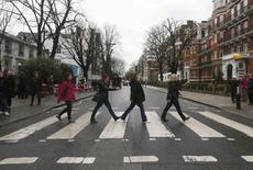 """Tourists walk on a zebra crossing to recreate the Abbey Road album cover by The Beatles, outside the Abbey Road recording studios in London, Britain March 9, 2016. George Martin, known as """"the fifth Beatle"""" for his work in shaping the band that became one of the world's most influential music forces, has died at the age of 90.  REUTERS/Neil Hall"""