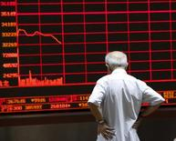 Un inversor mira un panel electrónico que muestra información bursátil, en una correduría en Pekín, China, 7 de julio de 2015. Las acciones chinas cayeron más de un 1 por ciento el miércoles, cortando una racha de avances de seis sesiones, luego de que un declive en los precios de las materias primas golpeó a los valores ligados a ese sector y llevaron a una toma de ganancias. REUTERS/Kim Kyung-Hoon