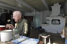 Селянин Иван Шамянок, которому 87, завтракает в своем доме в заброшенной деревне Тульговичи рядом с зоной отчуждения Чернобыльской АЭС в 370 километрах к юго-востоку от Минска 23 апреля 2012 года. Радиация в пище местных жителей по-прежнему на опасно высоком уровне, сообщила в среду Гринпис. REUTERS/Vasily Fedosenko