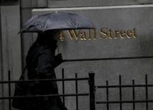 Las acciones caían ligeramente el lunes en la Bolsa de Nueva York, ya que un descenso en el precio del petróleo afectó a los títulos energéticos y los inversores evitaban hacer grandes apuestas antes de la publicación de una serie de datos económicos y la reunión de política de la Reserva Federal. En la imagen, un hombre pasea con un paraguas frente a la sede de la bolsa de Nueva York, en el distrito financiero, el 4 de marzo de 2016.  REUTERS/Brendan McDermid