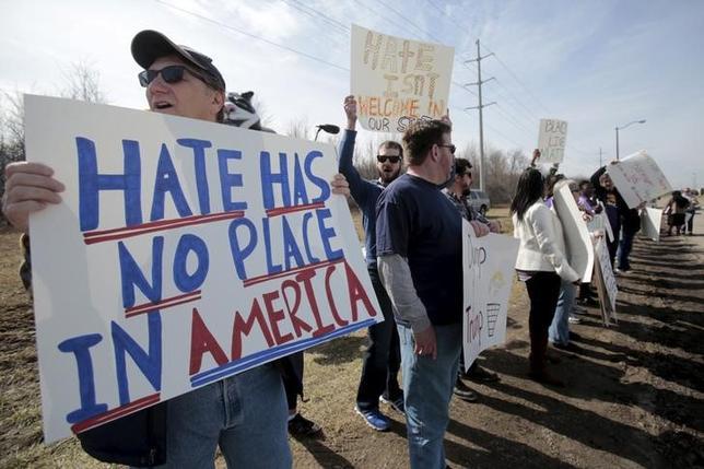 3月13日、米大統領選共和党候補のトランプ氏に反対する人たちは、さまざまな経歴を持ち、フェイスブックや無数の擁護団体を通して団結している。写真は「憎悪の居場所は米国にはない」などと書かれたメッセージを掲げる同氏に反対する人たち。オハイオ州で12日撮影(2016年 ロイターRebecca Cook)