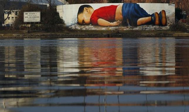 3月11日、独マイン川沿いに描かれたアイラン・クルディちゃんのグラフィティは、通勤する何千人もの人々の目にとまる。当時3歳だったアイランちゃんは、欧州へ海を渡る途中、母親と5歳の兄とともに命を落とした。フランクフルトで10日撮影(2016年 ロイター/Kai Pfaffenbach)