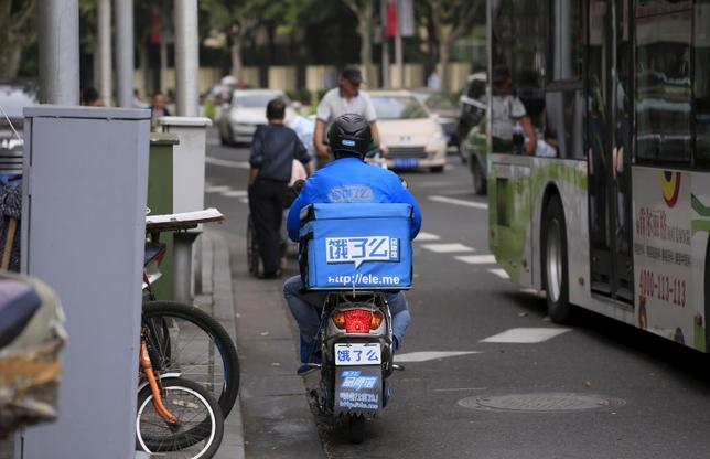 A courier of Ele.me food delivery smartphone application travels on his electric bicycle along a street in Shanghai, China, October 9, 2015.  REUTERS Aly Song