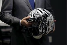 A representative holds a new impact absorbing helmet at the NFL Headquarters in New York December 3, 2015. REUTERS/Brendan McDermid