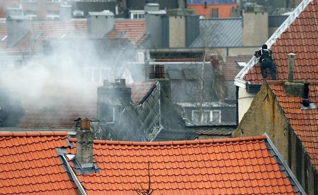 3月15日、ベルギーの首都ブリュッセルで、昨年11月のパリ同時多発攻撃の関連捜査をしていた警官らが発砲を受け、4人が負傷した。屋根から現場を監視するベルギーの警官(2016年 ロイター/Yves Herman)