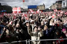 People wave Danish flags as they celebrate the 75th birthday of Denmark's Queen Margrethe, who is received at the City Hall, April 16, 2015. REUTERS/Mathias Bojesen/Scanpix Denmark