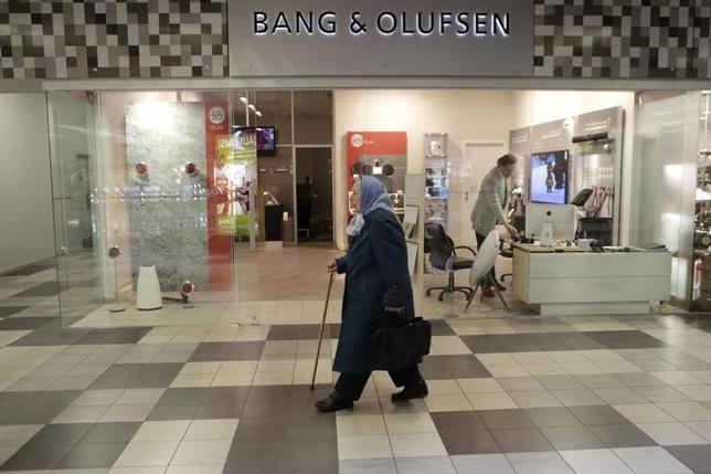 A woman walks past a Bang & Olufsen shop in Riga October 1, 2013. REUTERS/Ints Kalnins