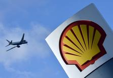 A passenger plane flies over a Shell logo at a petrol station in west London, in this January 29, 2015 file photo.  REUTERS/Toby Melville