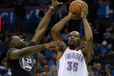 Feb 27, 2016; Oklahoma City, OK, USA; File photo of Oklahoma City Thunder forward Kevin Durant (35) shooting the ball against Golden State Warriors forward Draymond Green (23) during the fourth quarter at Chesapeake Energy Arena. Mandatory Credit: Mark D. Smith-USA TODAY Sports