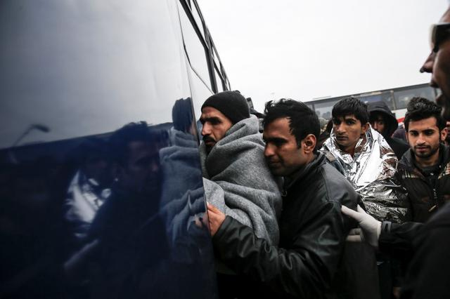 Refugees and migrants board a bus heading to the Moria registration centre, after arriving at the port of Mytilene on the Greek island of Lesbos, following a rescue operation by the Greek Coast Guard at open sea, March 22, 2016. REUTERS/Alkis Konstantinidis