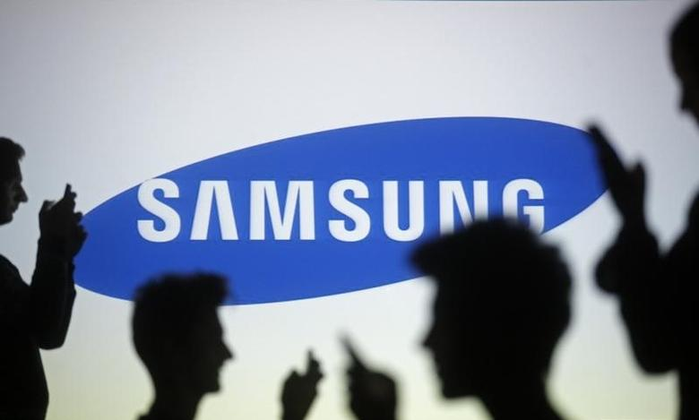 People are silhouetted as they pose with mobile devices in front of a screen projected with a Samsung logo, in this picture illustration taken in Zenica October 29, 2014.     REUTERS/Dado Ruvic/Files