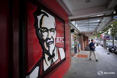 Посетитель у ресторана KFC в Шанхае 9 октября 2015 года. Yum Brands Inc, владеющий KFC и Pizza Hut, ведет переговоры с частными инвестиционными компаниями, в том числе KKR & Co LP и Hopu Investments, о продаже миноритарного пакета акций в своем некогда процветавшем китайском подразделении, готовясь к его выделению в отдельную компанию, сообщили в четверг два источника, знакомые с ситуацией. REUTERS Aly Song