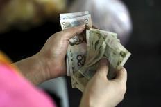 Un cliente sostiene billetes de 20 yuanes en un mercado en Pekín, 12 de agosto de 2015. El yuan chino se verá sometido a una renovada presión bajista si el dólar sube de manera significativa en los próximos meses, dijo el viernes un asesor de política del Banco Popular de China. REUTERS/Jason Lee