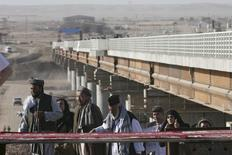 Афганцы переходят в Таджикистан по мосту через реку Пяндж 26 августа 2007 года. Боевики из Афганистана похитили двух дорожных рабочих из Таджикистана и еще одного ранили на территории, прилегающей к границе двух государств, сообщили Рейтер в пятницу источники в таджикском правительстве. REUTERS/Nozim Kalandarov