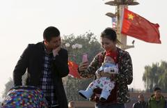 A couple takes pictures with their baby on the Tiananmen Gate in Beijing November 2, 2015. REUTERS/Kim Kyung-Hoon