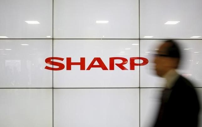 A man walks past Sharp Corp's liquid crystal display monitors showing the company logo in Tokyo, Japan, February 25, 2016. REUTERS/Yuya Shino