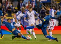 United States midfielder Graham Zusi (19) shoots the ball and scores his goal while Guatemala goalkeeper Paulo Motta (12) and defender Carlos Castrillo (13) defend in the second half of the game during the semifinal round of the 2018 FIFA World Cup qualifying soccer tournament at MAPFRE Stadium. Trevor Ruszkowski-USA TODAY Sports