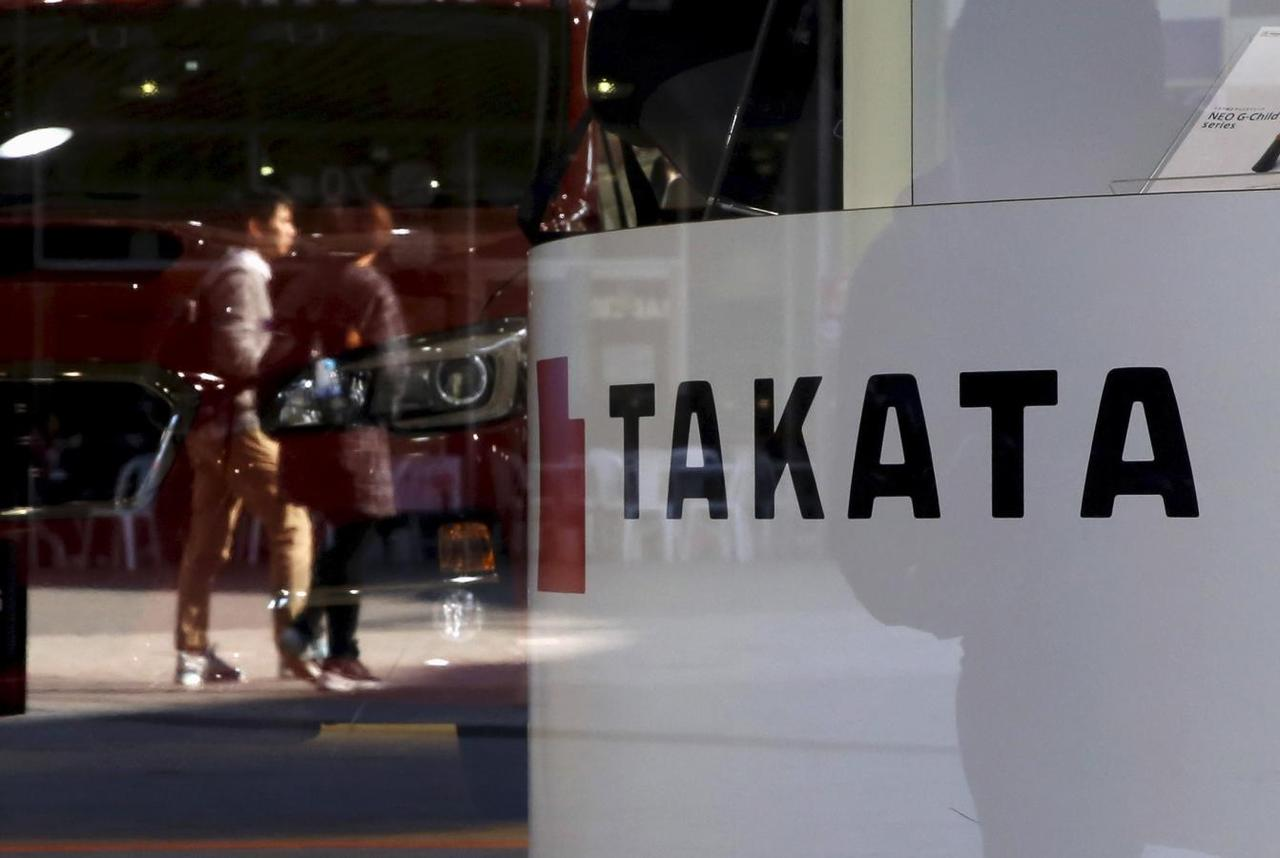 78642059c A logo of Takata Corp is seen with its display as people are reflected in a  window at a showroom for vehicles in Tokyo