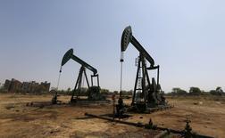 Unidades de bombeo de crudo fotografiadas en un campo petrolero en las afueras de la ciudad de Ahmedabad, India, 16 de marzo de 2016. Analistas petroleros elevaron sus pronósticos promedio para el precio del crudo en 2016 por primera vez en 10 meses, aunque advirtieron que la confianza de los inversores podría afectar las perspectivas a corto plazo sin una sólida mejora en los fundamentos del mercado, mostró un sondeo de Reuters. REUTERS/Amit Dave