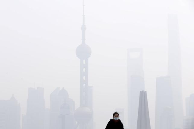 A woman wearing a face mask stands on a bridge in front of the financial district of Pudong amid heavy smog in Shanghai, China, December 15, 2015. REUTERS/Aly Song